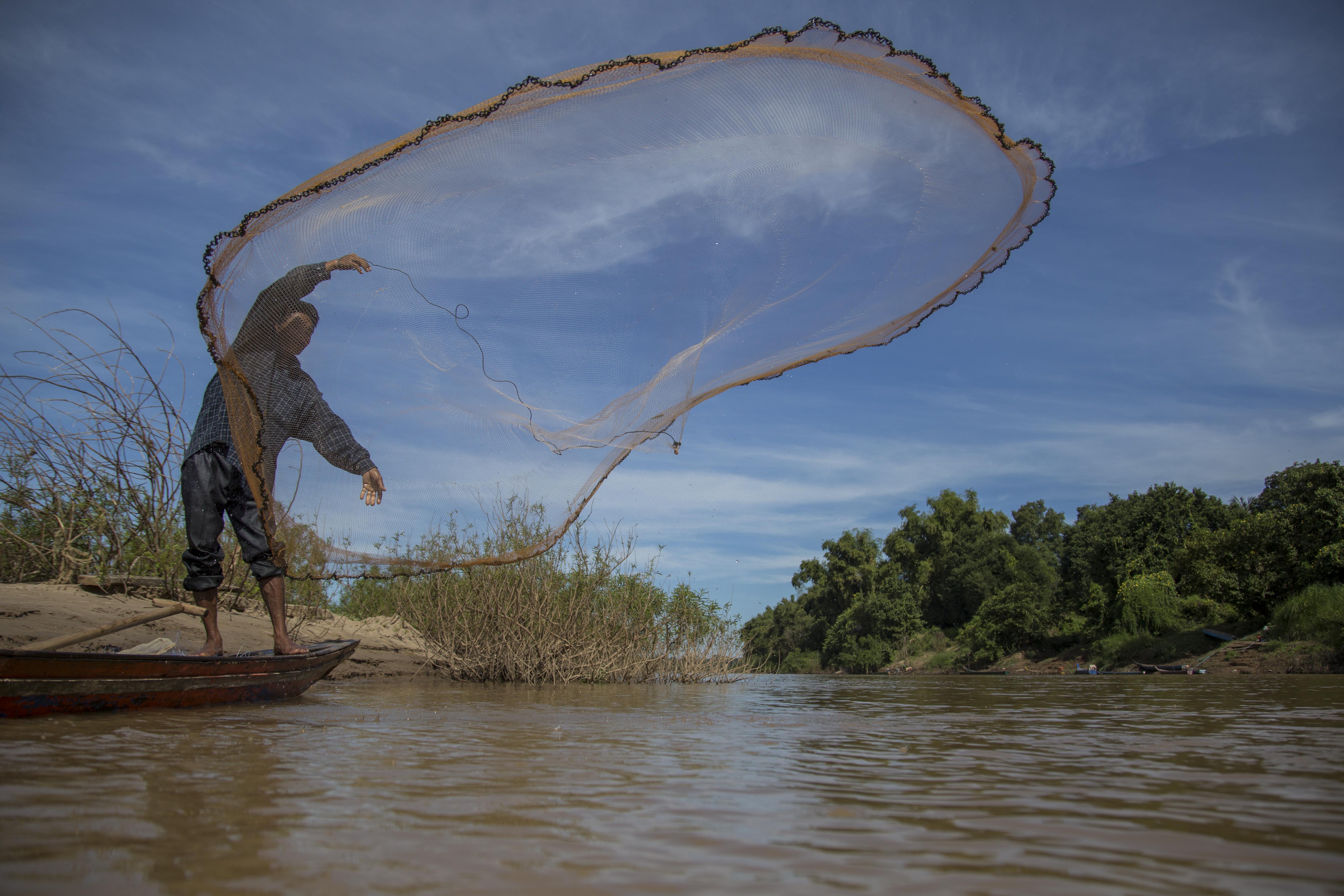 Kem Soth casts is net in the Mekong River. Photo by Savann Oeurm/Oxfam