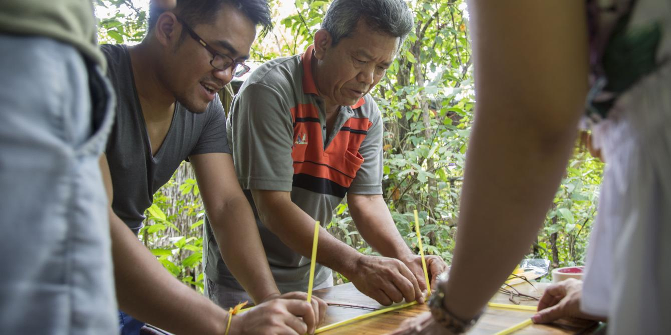 La (grey-orange shirt) works in a group, part of team building game, during annual program reflection in Tatai, Koh Kong, 2017. Photo: Seiha Tiep/Oxfam.
