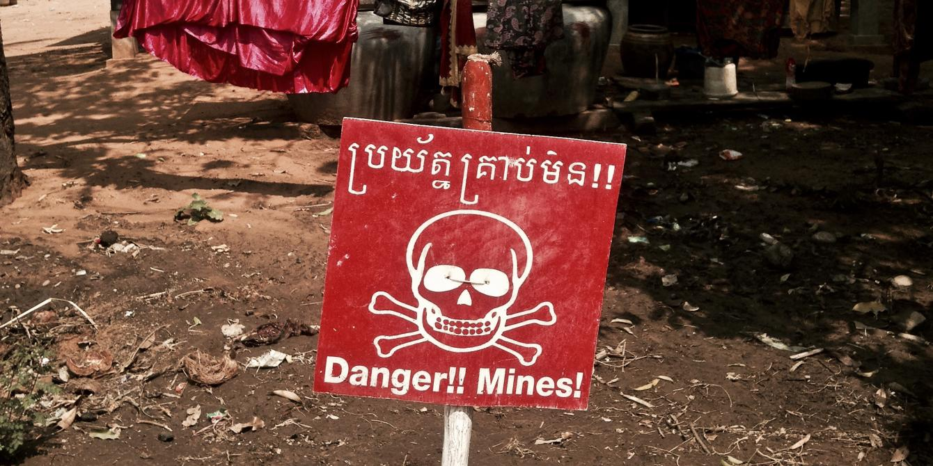 Signs warn of land mine danger in Kouk Sangkerch village, a deadly legacy of 20th century conflicts. Photo by Patrick Brown/Panos for Oxfam America