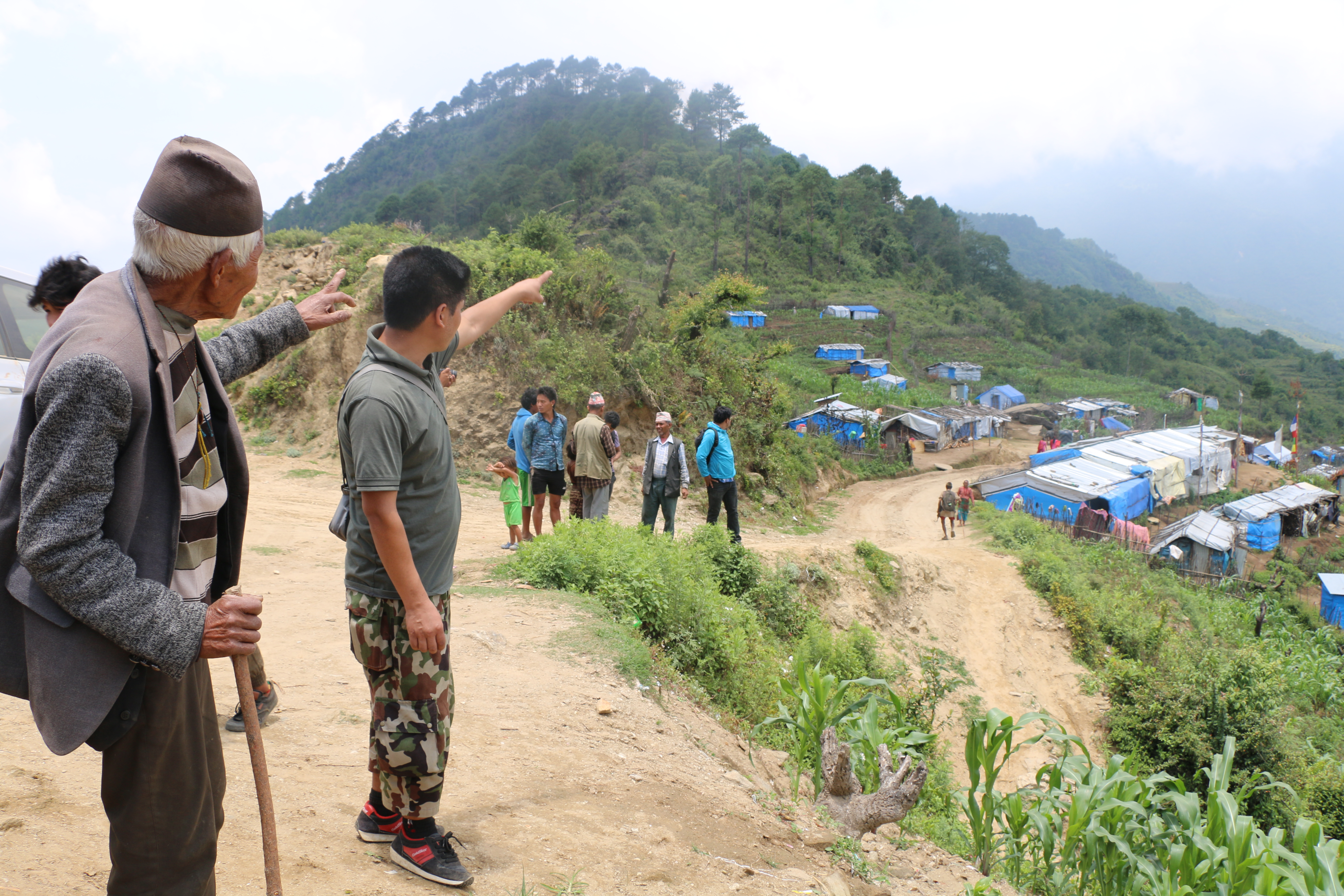 Gyalbu Sherpa (left) and his son, now living in Selang as internally displaced people, pointing towards their place of origin