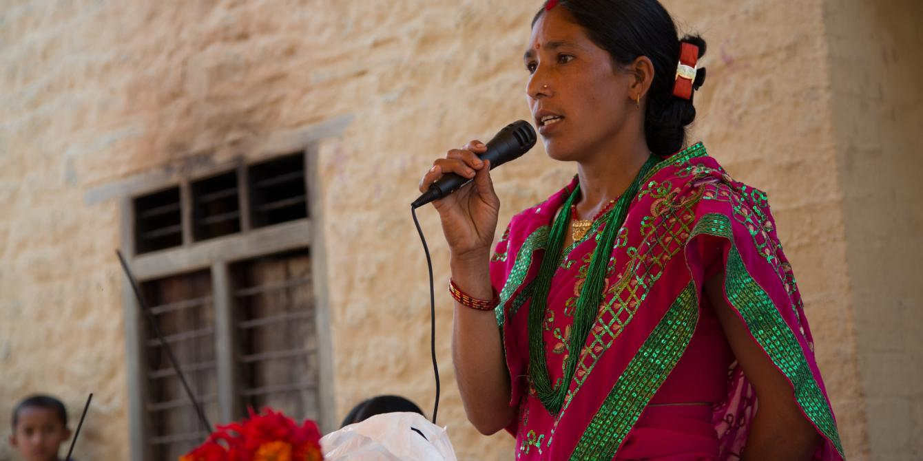 Janaki Oli (28) performs as the master of ceremonies at an event organised by the seed production group in Satmule, Surkhet, Nepal to celebrate International Women's Day - Credit: Aubrey Wade/Oxfam