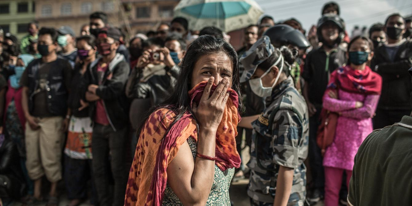 A woman breaks down when a crowd gathers to watch a digger remove rubble from a collapsed building in Gongabu, Kathmandu - Credit: Pablo Tosco/Oxfam
