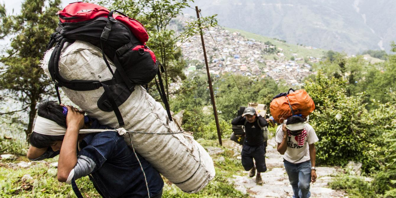 Porters carry relief goods up to remote Laprak village in Gorkha district - Credit: Sam Pickett/Oxfam