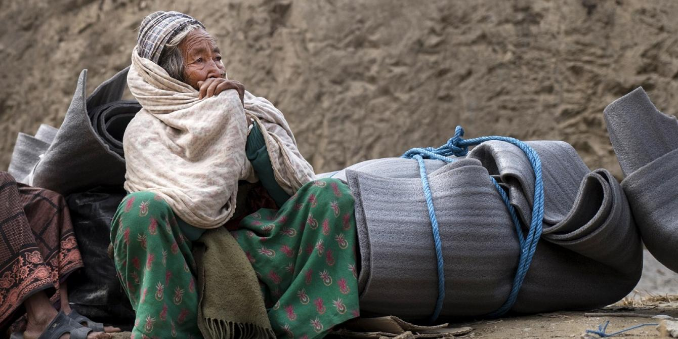 An elderly earthquake survivor waits for transport after receiving a Winterisation Kit - Credit: Kieran Doherty/Oxfam