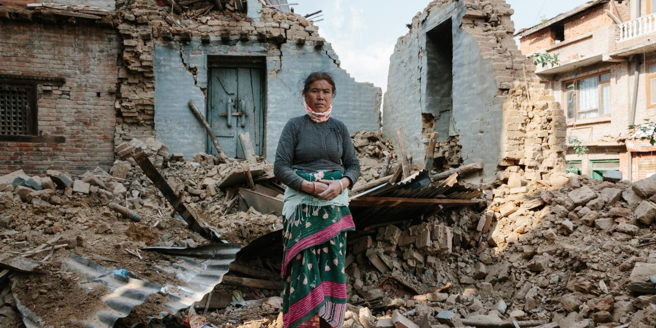 An earthquake survivors stands by her collapsed house - Credit: Aubrey Wade/Oxfam
