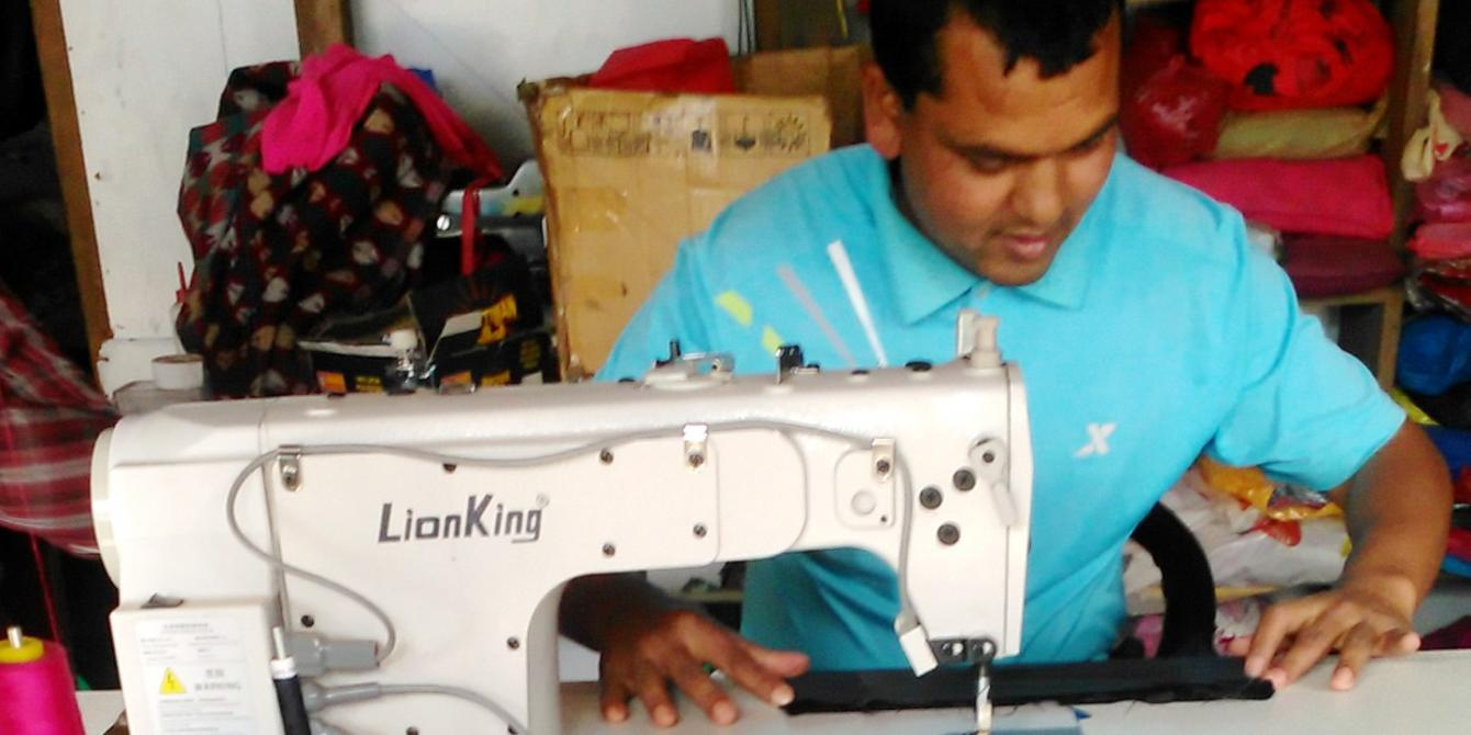 Raju Bishwokarma stitching clothes using his new electric sewing machine. Photo by: Animesh Rai/Oxfam