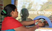 A woman takes out money send by her husband from India from her account - Credit: Oxfam/IOM/UNDP