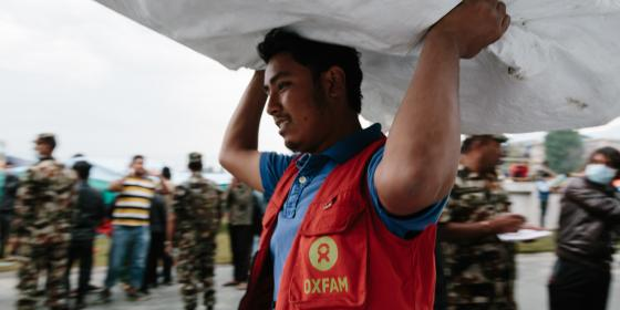 Oxfam volunteer Shekhou Khadka (23) works to off load latrines being delivered to the Tundikhel IDP camp in Kathmandu, Nepal. He is one of 500 volunteers trained to react in the event of an earthquake during the urban risk management program - Aubrey Wade/Oxfam