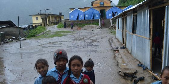 Students navigate the muddy entrance to the government school in Dunche, Rasuwa district, during monsoon. They study in tents and temporary shelters - Credit: Lucia de Vries/Oxfam