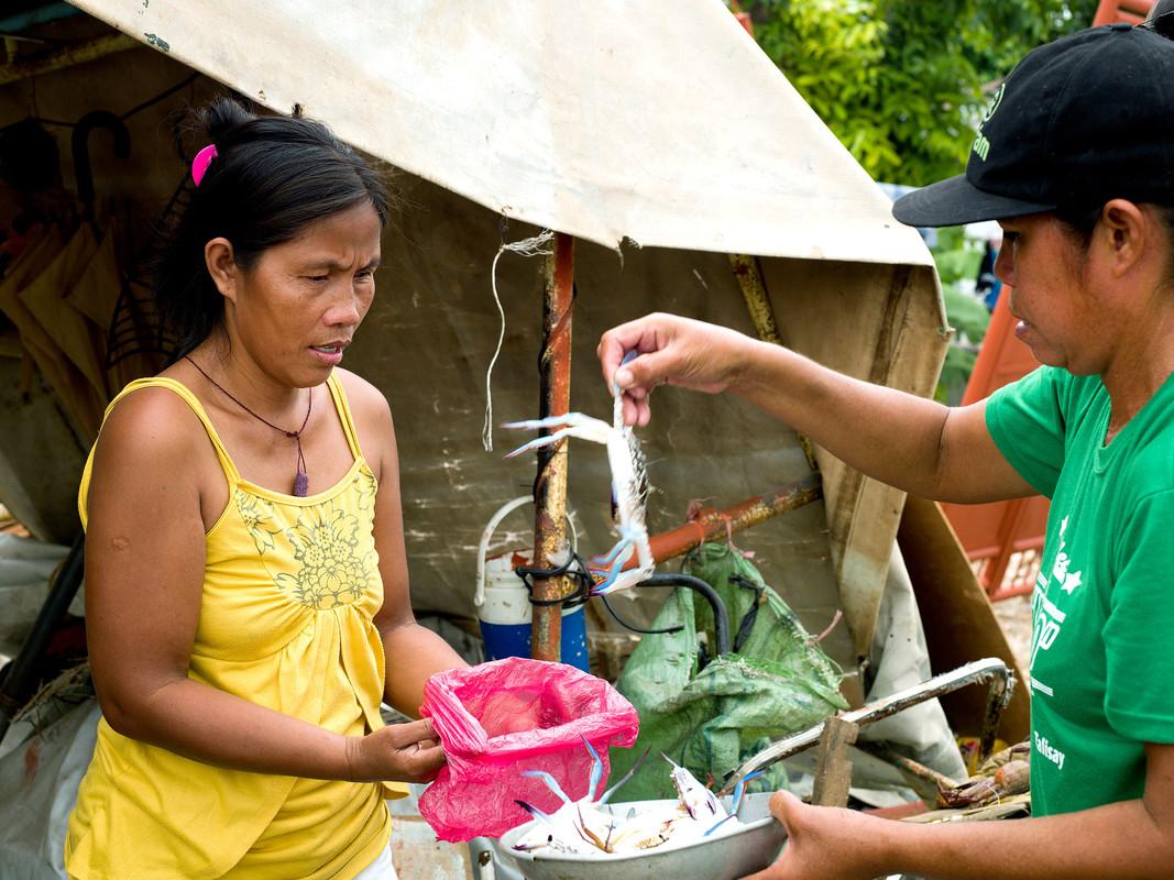 Fish Saleswoman Imelda Esgana (47) stands next to a fishing boat in Talisay, Bantayan. (Photo: Tessa Bunney/Oxfam)