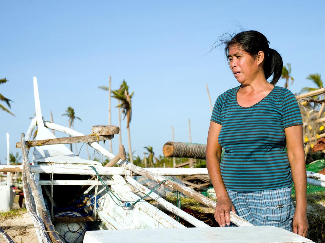 Fish Saleswoman Imelda Esgana (47) stands next to a fishing boat in Talisay, Bantayan. (Photo: Tessa Bunney)