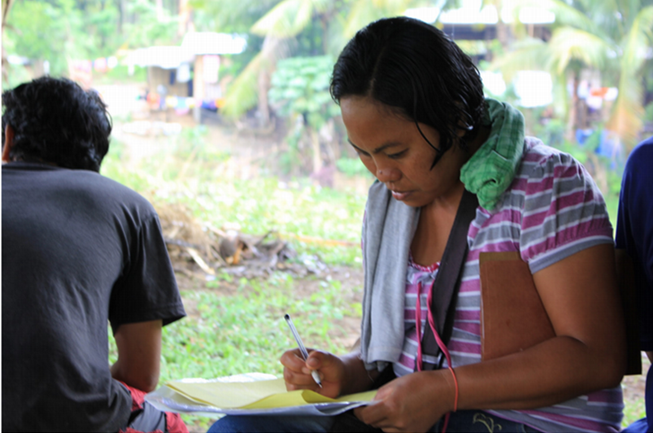 Charito, 34 years old, carefully notes new lessons she has learned from the farmers school held  in Bagumbayan in Sultan Kudarat, her hometown.(Photo: Genevive Estacaan/Oxfam)