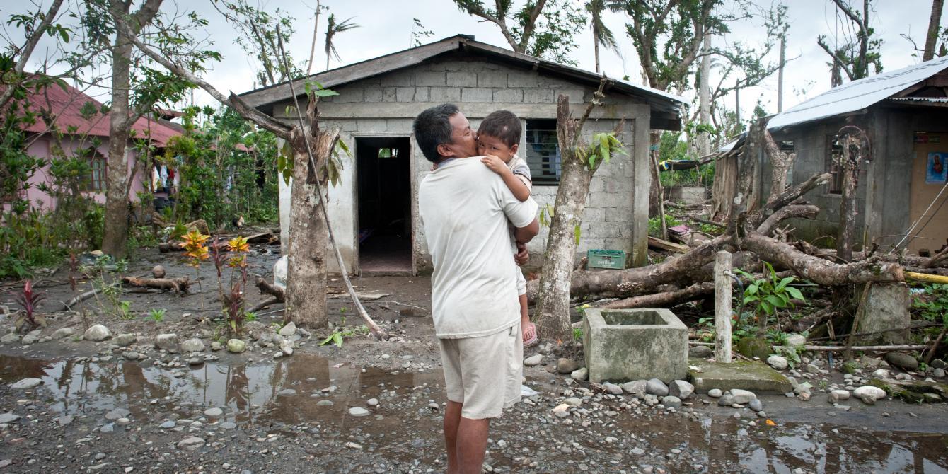 Zacarias Latina carries his son Renzel Jake (3) in Julita, Leyte (Photo: Eleanor Farmer/Oxfam)
