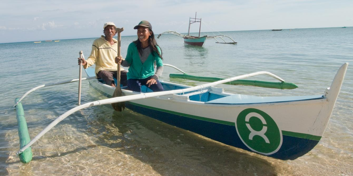 """Chanley and her father, Gregorio, are also pleased about having their boat fixed. They no longer have to rent a neighbour's boat, which cuts into their modest profit. Chanley says they can """"start to get back to our fishing like before and support ourselves"""". """"I feel really happy about this,"""" she adds. (Photo: Caroline Gluck/Oxfam)"""