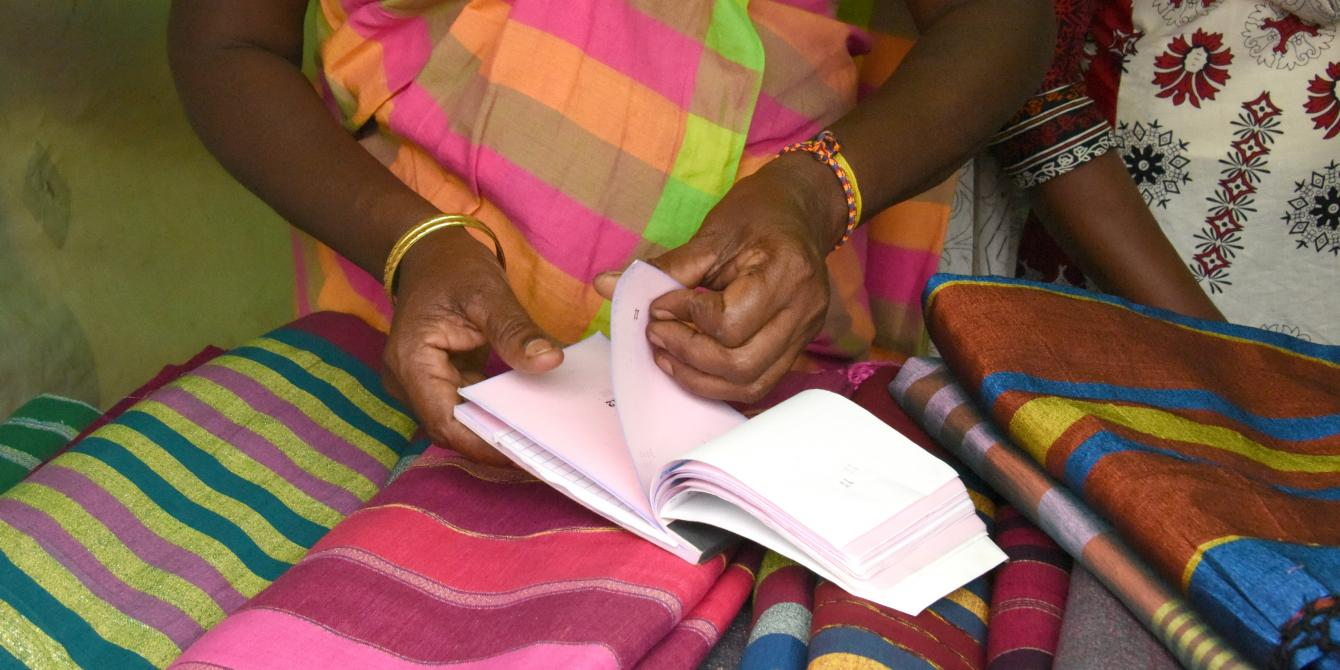Woman flipping through a receipt book. Photo credit: Sheshadri Kottearachchi