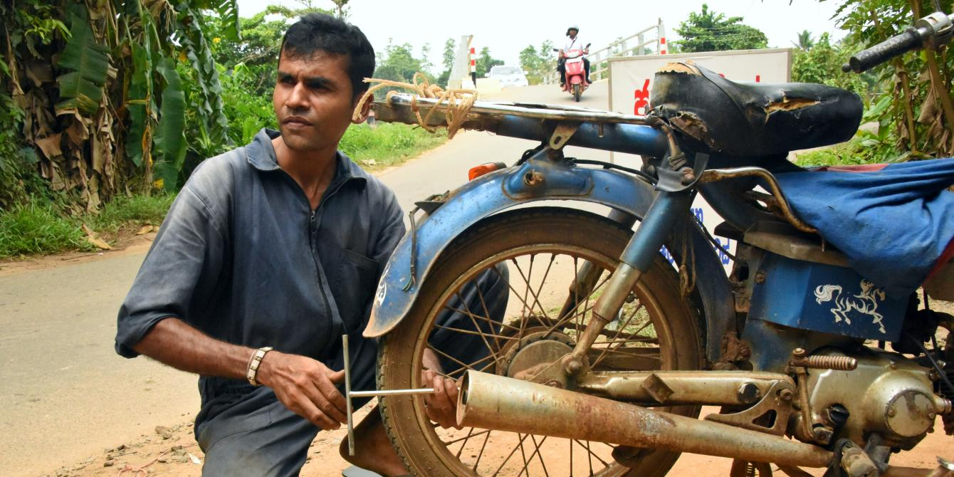 Sri Lankan mechanic working on a motorcycle