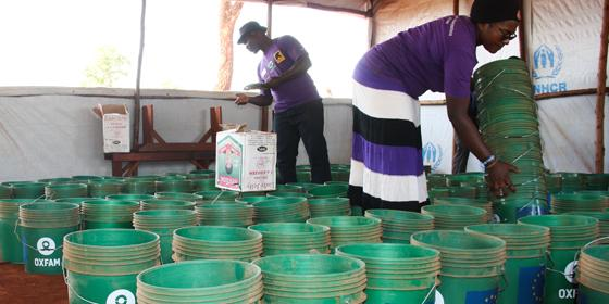 Public Health Promoters counting buckets before distributing to the women refugees (Photo by Yussuf Kajenje)