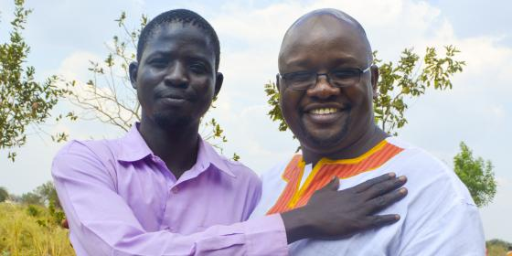 Oxfam's Uganda Country Director Peter Kamalingin shares a light moment with Deng Bol, a teacher who sought refuge from conflict in South Sudan by crossing the border into Uganda.