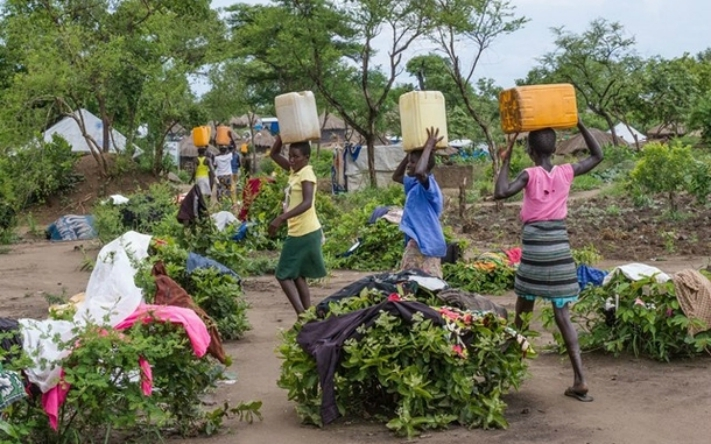 At the Bidi Bidi refugee settlement in Uganda, women carry water back to their shelters. The settlement is now home to more than 287,000 refugees. Photo by Coco McCabe/Oxfam